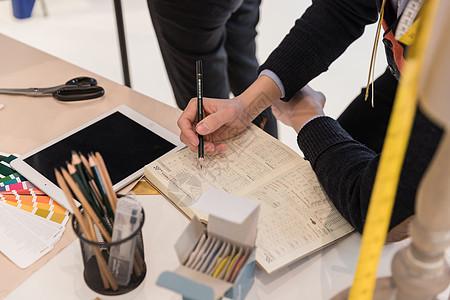 男服装设计师用本子记录特写图片