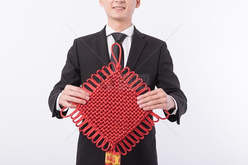 年轻男性手拿红色中国结图片