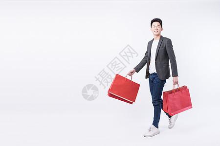 提着购物袋开心购物的年轻男子图片
