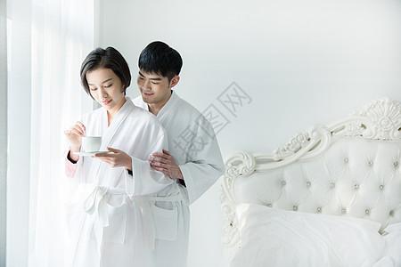 年轻夫妇穿浴袍在卧室图片