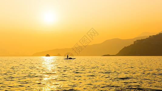 夕阳中海面船只与远山剪影图片