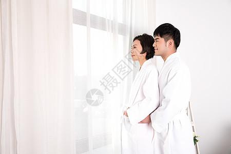 情侣穿着浴袍站在窗边图片