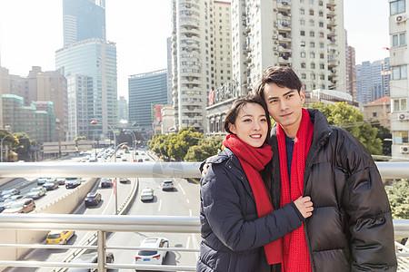 年轻情侣天桥上看城市风景图片