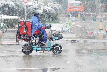 寒冷冬季马路骑电动车的外卖人员图片