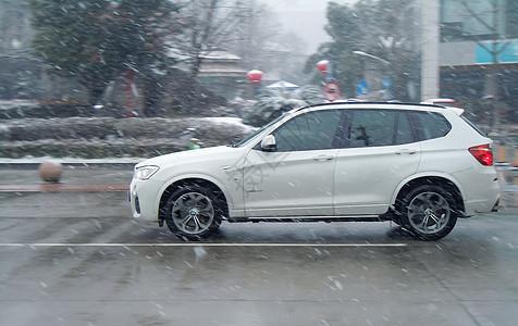 雪中马路上行驶额汽车图片
