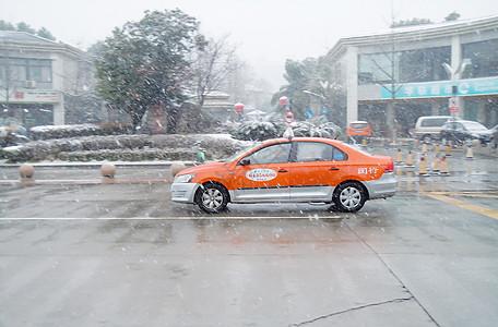寒冷冬季雪中行驶的出租车图片