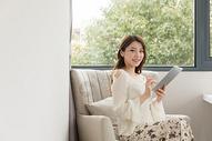 年轻女性在卧室放松看平板电脑图片