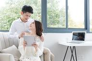 情侣坐在沙发上一起看平板电脑图片