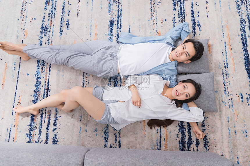 年轻情侣开心躺地毯上图片