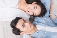 年轻情侣相依偎躺地毯上图片