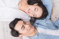 年轻情侣相依偎躺地毯上500817552图片