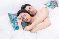 年轻夫妻拥抱躺床上休息图片