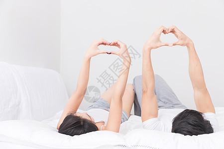 年轻夫妻躺床上比心图片