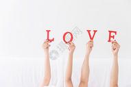 年轻夫妻躺床上手拿LOVE特写图片