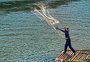 竹排上撒网的渔民图片