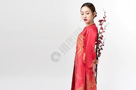 身着红装的美女手持梅花图片