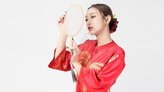 穿着红装的美女手持蒲扇图片