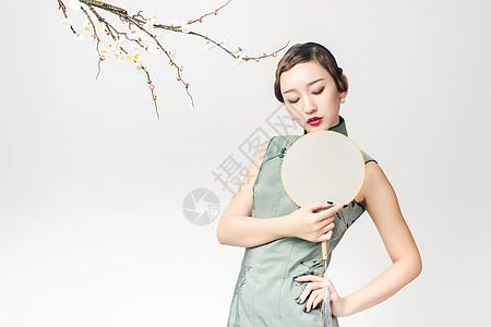 梅花树下的旗袍美女手持蒲扇图片