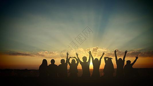 夕阳下庆祝的团队图片
