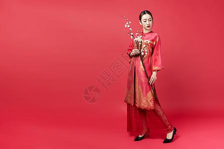 红妆美女抱着梅花图片