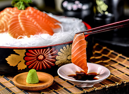 筷子夹起来的三文鱼刺身图片