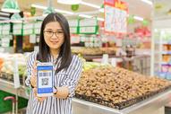 超市年轻女性手拿手机支付图片