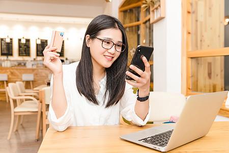 咖啡馆内年轻女性在网购图片
