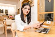 咖啡馆内年轻女性看手机图片