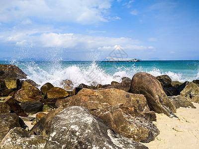 浪花拍打着海滩边的巨石图片