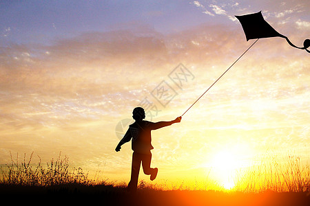 黄昏下放风筝的男孩图片