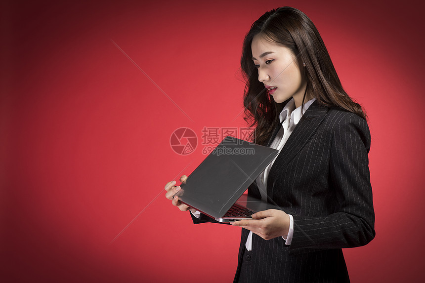 拿着条记本的职业女性图片