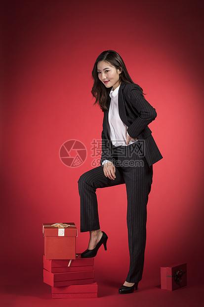 脚踩礼物盒的职业女性图片