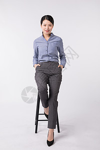坐在高脚登上自信的商务女性图片