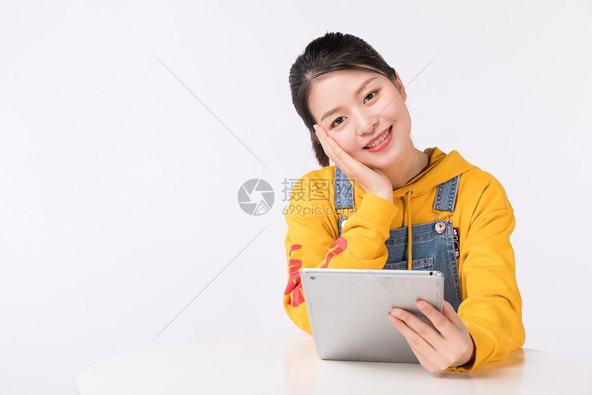 坐着运用平板电脑的时髦女生图片