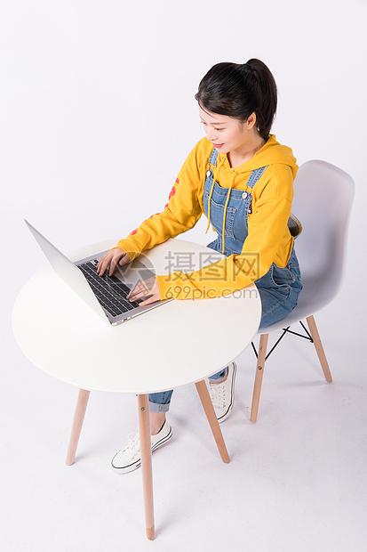 坐在椅子上运用电脑的先生图片