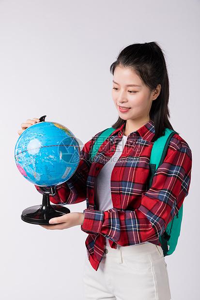 拿着地球仪背着书包的先生图片
