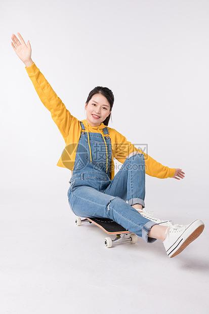 坐在滑板上的芳华美少女图片