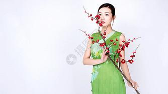 梅花树下身着绿色旗袍的美女图片