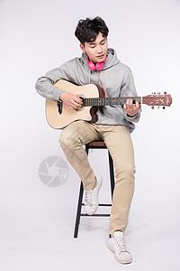 微笑着弹吉他的阳光男孩图片