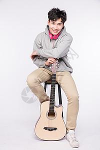 坐在椅子上拿着吉他的年轻男生图片