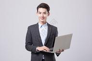 青年商务男性手拿电脑图片