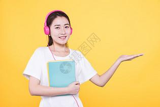 青春学生抱着书听音乐图片