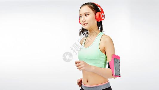 青年女性跑步使用电子产品图片