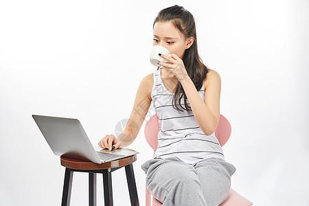 青年女性喝着开飞使用电脑办公图片