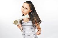 青年女性吹头发图片