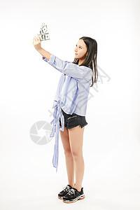 年轻女孩拿着钱期盼的表情图片