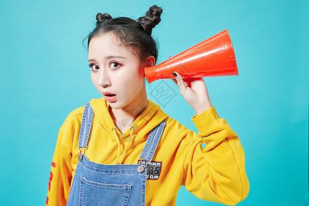 青年女性拿着听筒听的动作图片