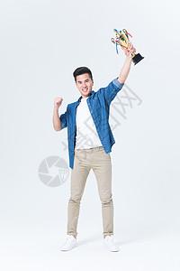 年轻男性高举冠军奖杯图片