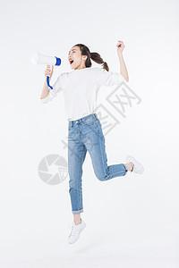 拿喇叭喊话跳跃的青年女孩图片