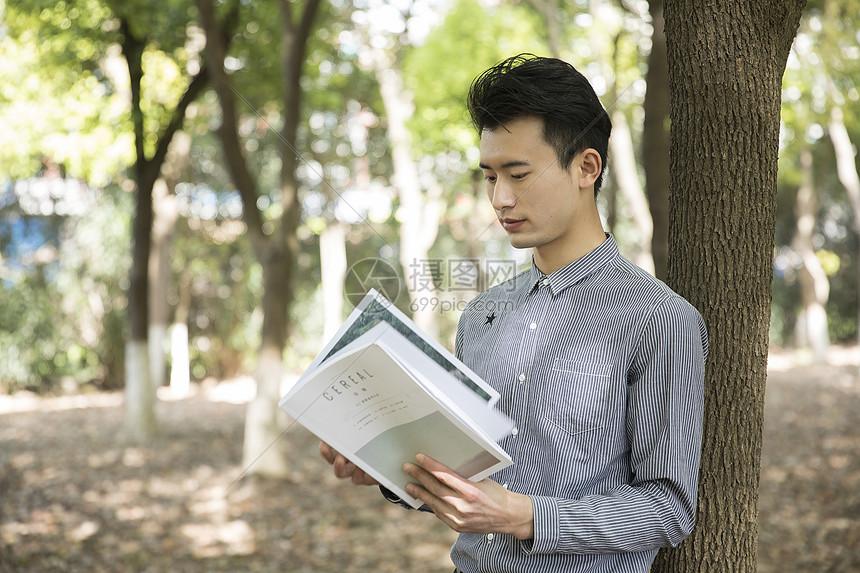 男士在树林里阅读图片